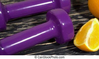 Oranges, dumbbells and measuring tape on wooden background....