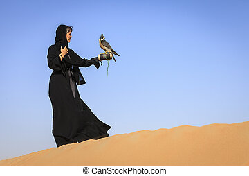 Woman with Peregrine Falcon - A woman in abaya with...