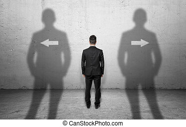Businessman standing in front of a concrete wall with arrows...
