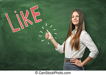 Young beautiful woman with thumbs up gesture standing near big red word 'like' written on green chalkboard.