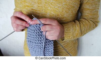 woman's hands knitting needles