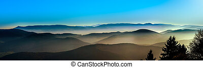 Aerial view of colorful autumnal mountains, foggy sunset,...