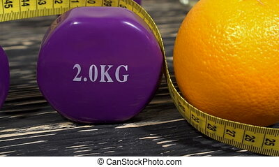 Oranges, dumbbells and measuring tape on wooden background....