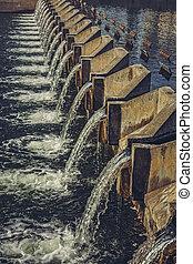Concrete weir across river - Water cascading through...