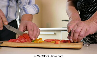 Senior man and a woman of cut vegetables in the kitchen. Carefully cut the tomatoes for the salad. Healthy food concept