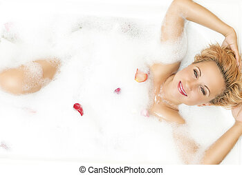 Portrait of Passionate Alluring Sensual Caucasian Blond Resting in Foamy Bathtub Filled with Rose Petals During Skin  Treatment