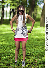 Portrait of Happy Laughing African American Teenager With Dreadlocks Posing Outdoors.