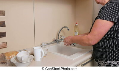 Woman aged washes dishes at home on huhne. She gently wipes the cup and fork sponge. It uses a detergent
