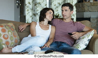 Happy and lovely young couple at home in sofa watching tv together, man holding remote control