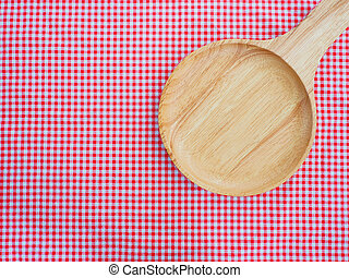 Empty plate on red checked tablecloth.