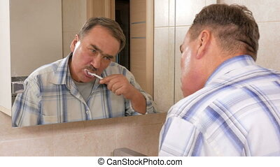 Senior man mustache brush your teeth in the bath. He spits out excess toothpaste in the sink. The concept of purity