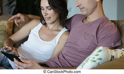 Young couple shopping on internet with tablet, sitting on a couch, side view