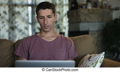 Serious good looking man working on his laptop while sitting on a couch in the living room