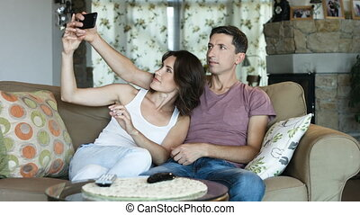 Beautiful young couple is making selfie using a smart phone and smiling while sitting on sofa at home.