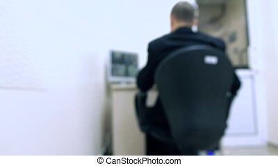 Blurred security guard at surveillance monitor 4K video -...