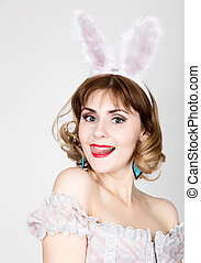 beautiful young woman in pink dress and rabbit ears,...