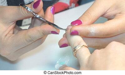 Manicurist uses professional manicure tool. - manicure...