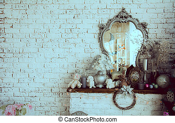 Background brick wall with a mirror. Toys and figurines on...
