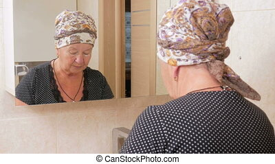 Senior woman in bathroom applying anti-aging lotion. You can...