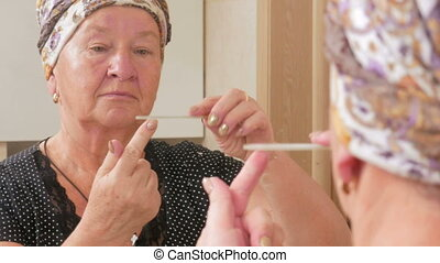 Woman aged makes a manicure yourself in the bath. It uses a...