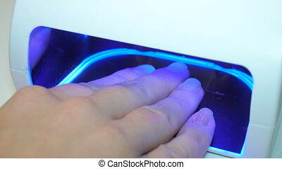 UV lamp for drying nails with gel method. a manicure in the...