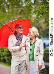 Enjoying rainy day - Beautiful senior couple enjoying...