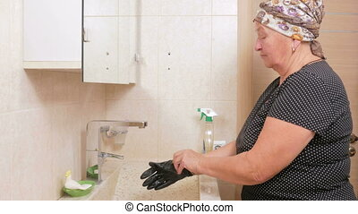 Senior woman cleans the sink in the bathroom of the hotel room. She uses gloves and cleaner. In the hands of a sponge for washing