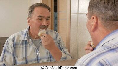 Senior man of shaving in the bathroom. It uses shaving foam...