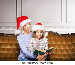 Mother and daughter reading a book at home