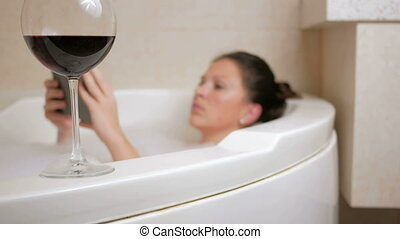 Beautiful girl taking a bath with foam and tablet PC. A large white bath and a glass of red wine. Clicks on the plate and drinking wine