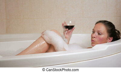 Beautiful girl taking a bubble bath with a glass of wine. A large white bath and joy on his face. relaxation concept