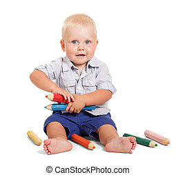 Cheerful little boy sits and holding large pencils isolated....