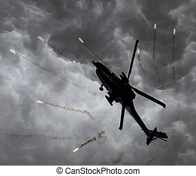 Silhouette of an attack helicopter firing flares, storm is...