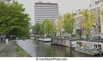 Barges and houseboats at the Amstel canal in Amsterdam, Netherlands