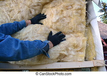 Builder hands insulating wooden house with mineral wool -...