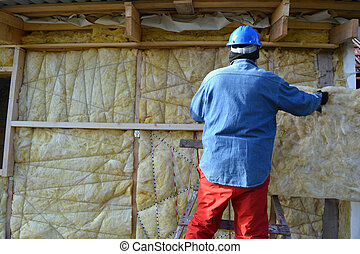 Builder insulating wooden house with mineral wool - Builder...