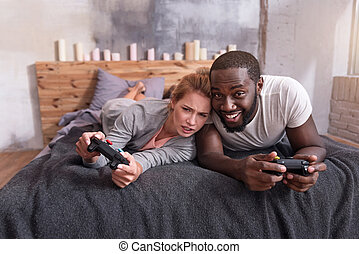 Overjoyed couple enjoying video games in bed - Sweet family...