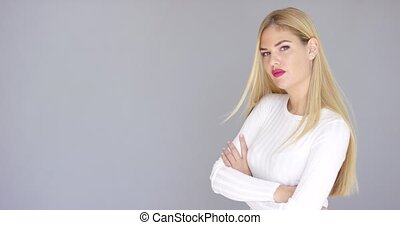 Self-assured young blond woman standing with folded arms...