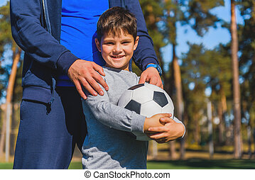 Happy kid with ball near parent