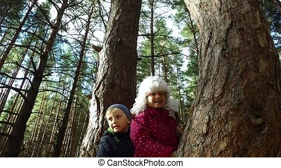 Boy and girl sitting on a large tree. The children have...