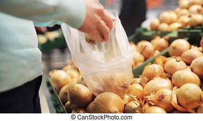 woman putting onion to bag at grocery store - shopping,...