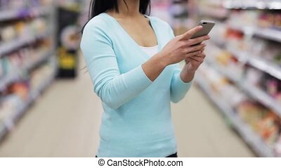 woman with smartphone at supermarket or store - shopping,...
