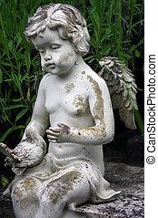 little angel sculpture decorate in small garden - a little...