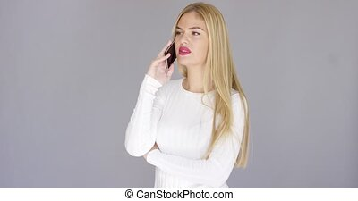 Pretty young woman laughing on a mobile - Pretty young blond...