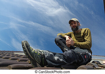 bearded roofer resting on top of a roof sunny day