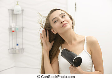 Beautiful young woman looking at the mirror drying hair -...