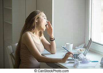 Profile portrait of attractive woman yawning at the laptop