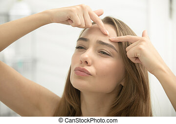 Young woman troubled checking wrinkles on her forehead