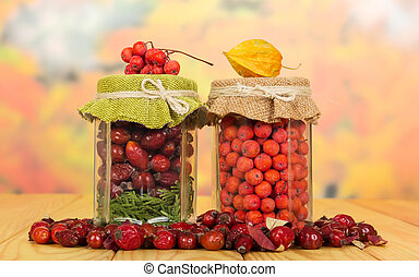 Jars with berries mountain ash, wild rose on autumn leaves -...