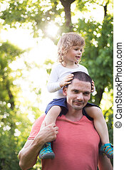 Father carrying his son on his shoulders. Sunny summer.